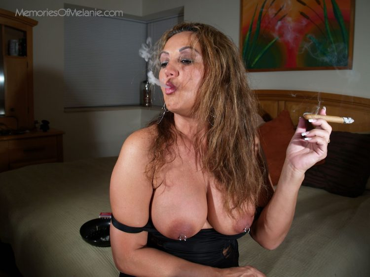 Big tit topless mature Latina, Melanie, smoking a cigar. in her bedroom.