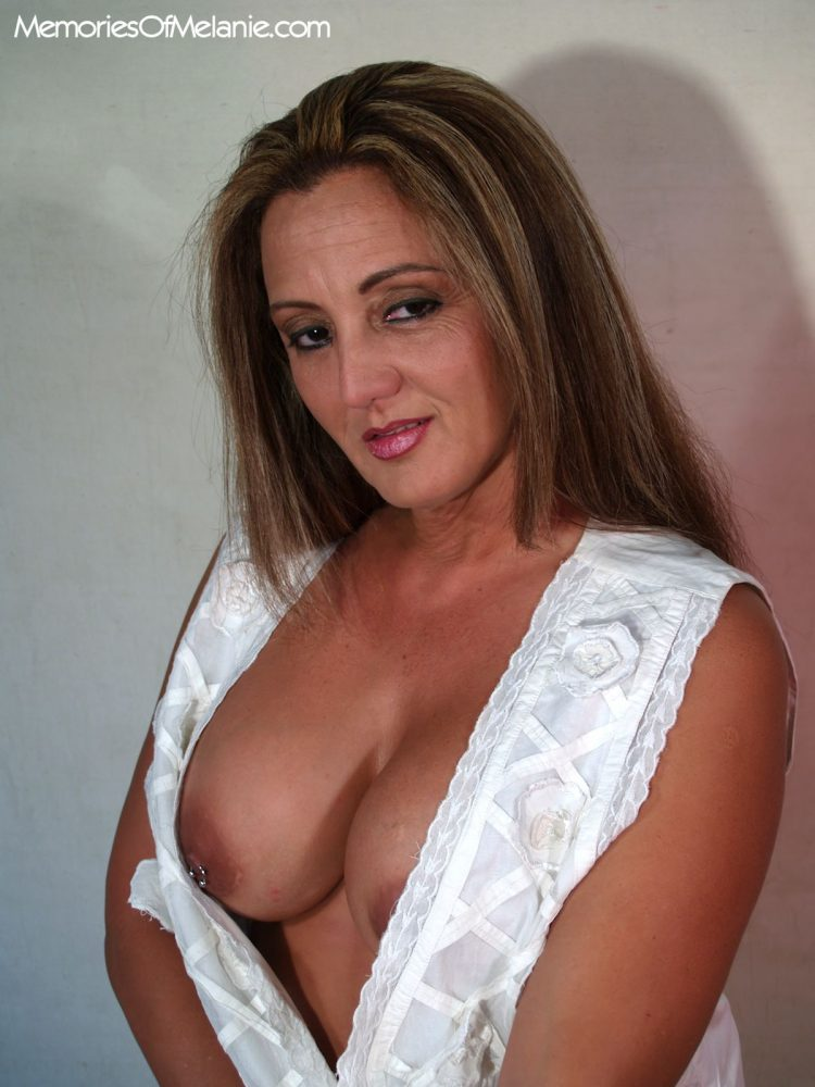 Mature Latina mom exposes her boobs and pierced nipples.