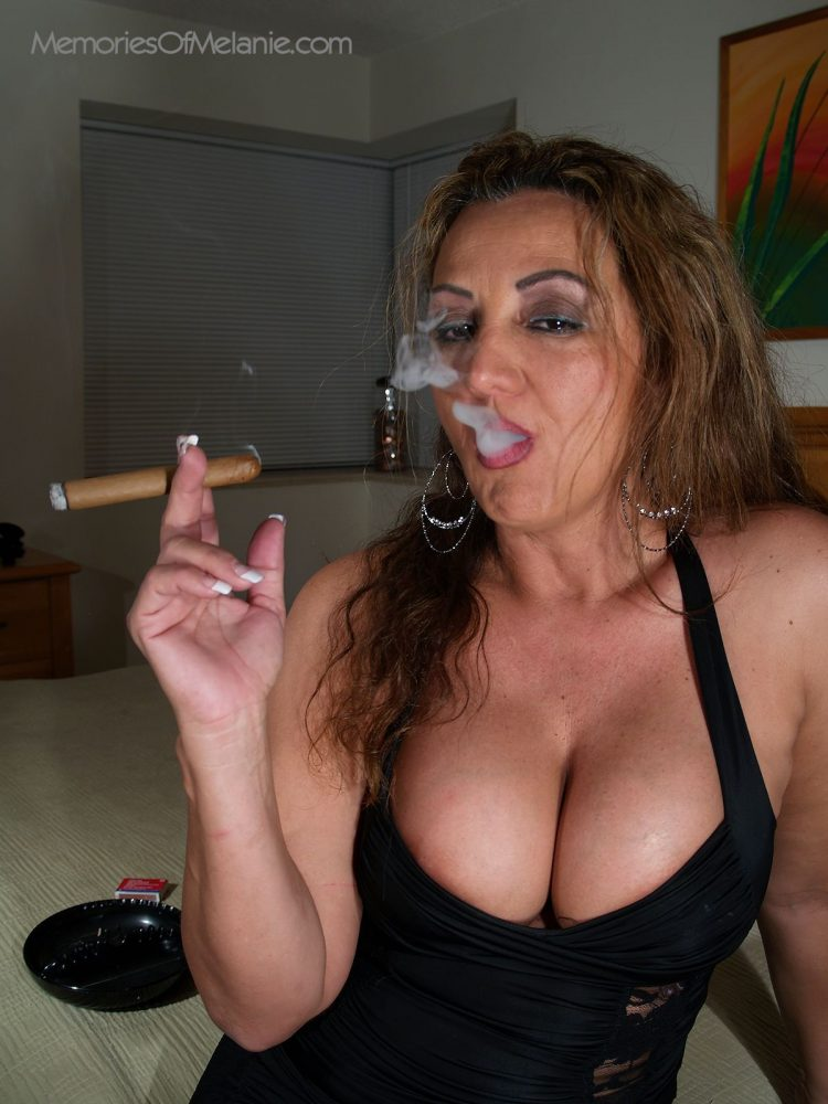 Busty wife smoking a cigar in her bedroom.
