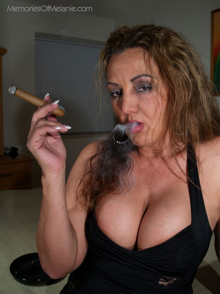 Big boobed mature mom smoking a cigar and showing deep cleavage.