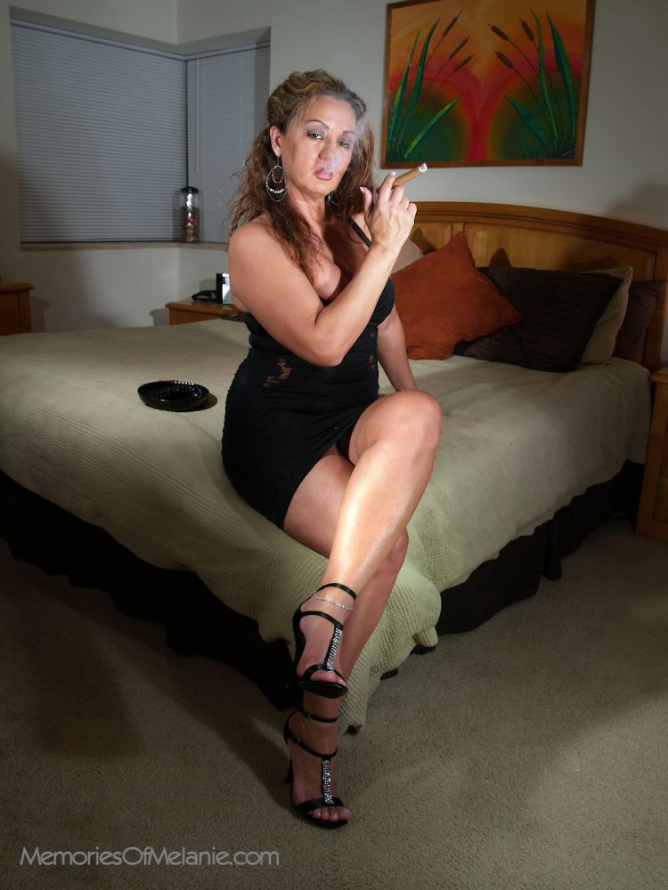 Glamour babe, smoking a long stogie in her bedroom.
