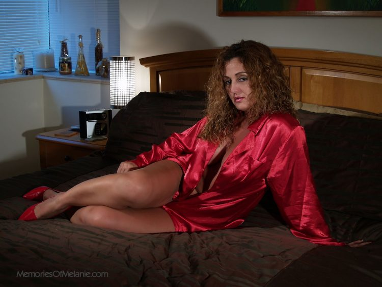Latina mom in bed wearing her high heels and showing cleavage.