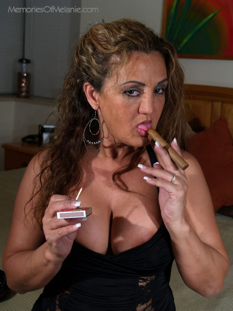Big boobed mom lights-up her long cigar.