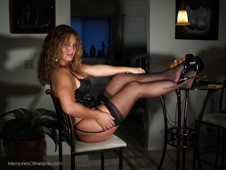 Stripper glamour babe in stockins and high heels with deep cleavage.